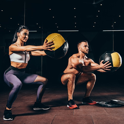 A man and woman doing a medicine ball workout.