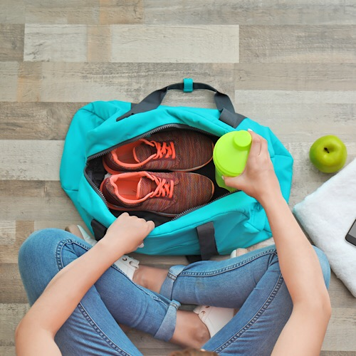 Young woman packing sports bag on floor, top view.