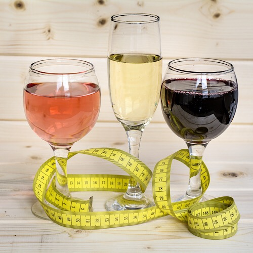 Three different glasses of wine with measuring tape wrapped around them.