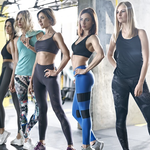 Sexy sportive girls are posing in the gym on the windows background. They are wearing multicolored sportswear: tops, sleeveless, pants and sneakers. Woman are looking forward. Horizontal. - Image