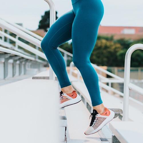 A woman in teal leggings jogging.