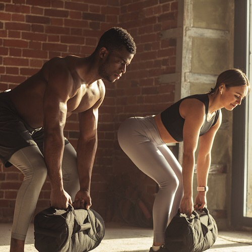 Young mixed-race fit couple doing squats exercise, while holding in hands heavy sandbag during group circuit functional training at the well-lit gym with panoramic windows. - Image