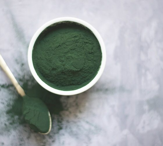 Powdered green supplement on a cup and a spoon.