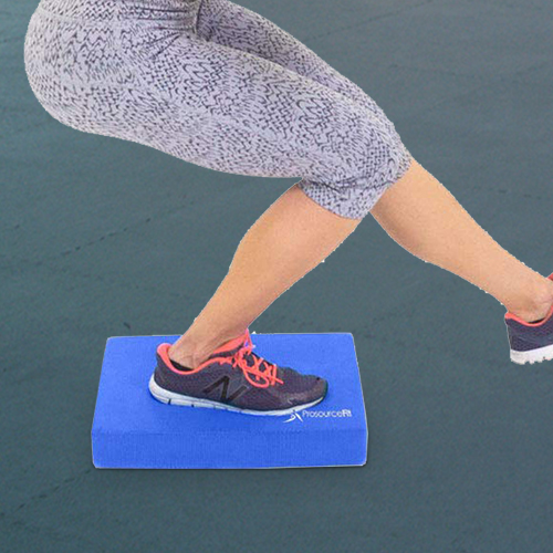 A woman balancing with one foot on the airex pad.