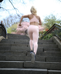 Fit girl running up steps for a workout.