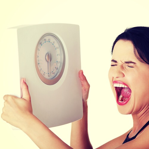 An image of a woman frustrated with her weight.