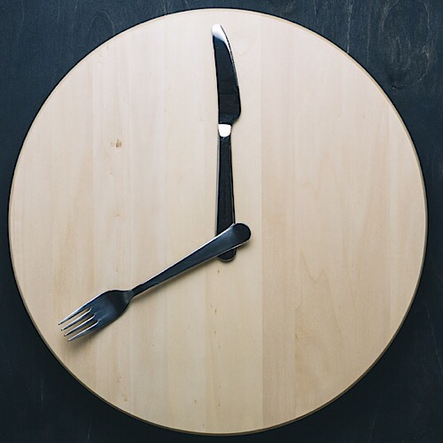 an image of a wooden wallclock with knife and fork as hands.