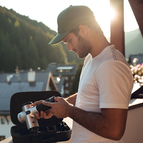 An image of a man holding the hyperice hypervolt.