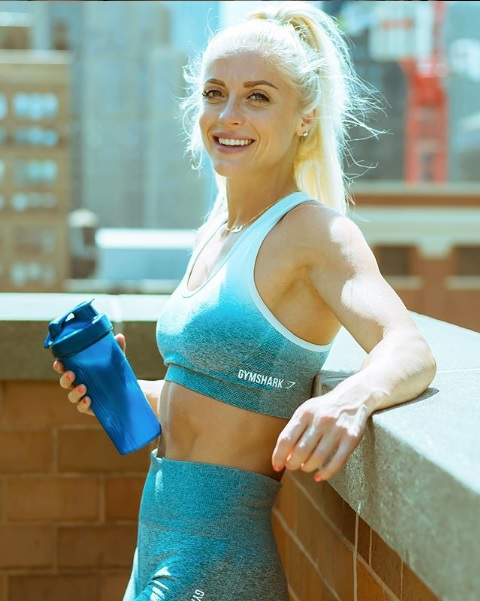 Fit girl with shaker bottle smiling in the city.