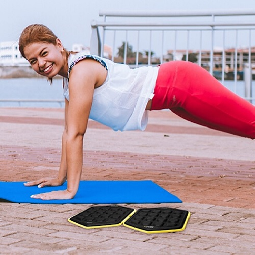 A fit woman doing push ups on a yoga mat beside the slidez-disc.