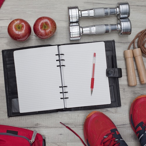 A fitness journal on a table next to 2 apples a dumbbell a jumping rope and a pair of shoe.