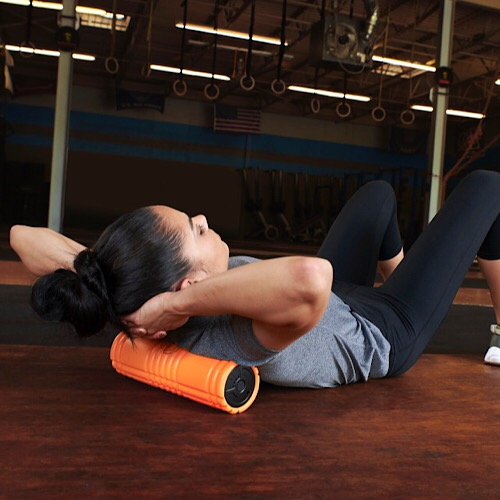 A woman using the vibrating foam roller.