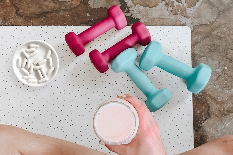 2 pairs of dumbbells, cup of tablets and next to a woman holding a glass of supplement drink.