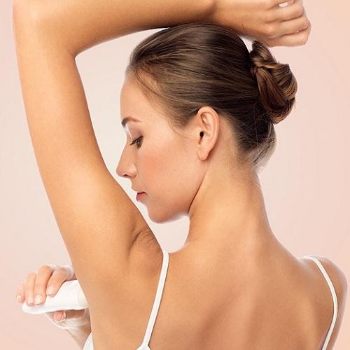 A women putting on a deodorant.