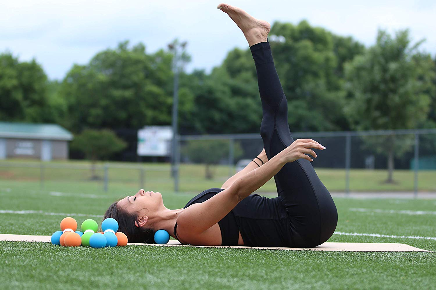 a woman stretching with lacrosse balls