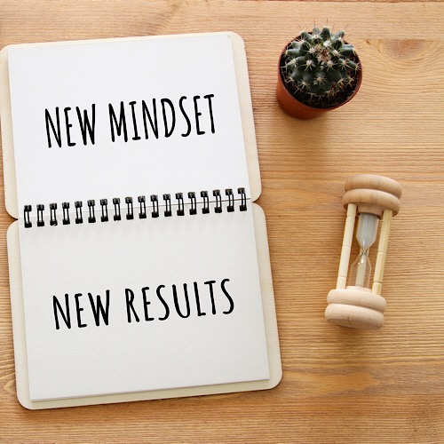 A print saying new mind set new results on a notebook.