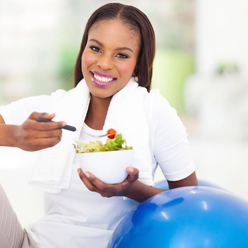 beautiful young african woman eating vegetable green salad - Image