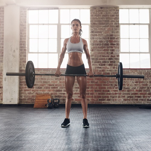 Full length portrait of muscular woman in a gym doing heavy weight exercises. Fitness female doing weight lifting at health club. - Image