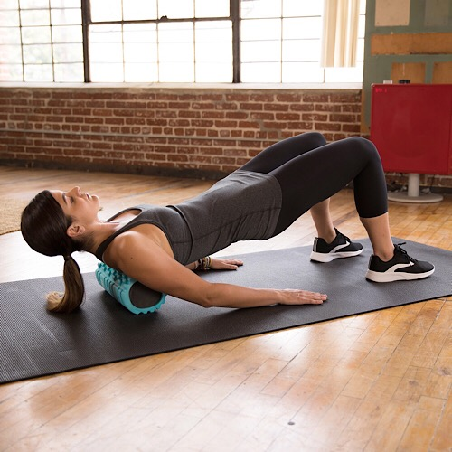 A woman using a foam roller on her back