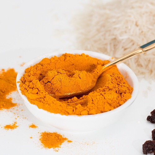 A bowl full of turmeric powder with a spoon.