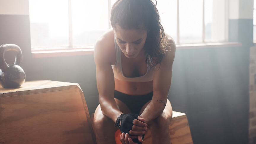 Young woman sitting on a box at gym after her workout and looking down. Female athlete taking rest after fitness training at gym. - Image