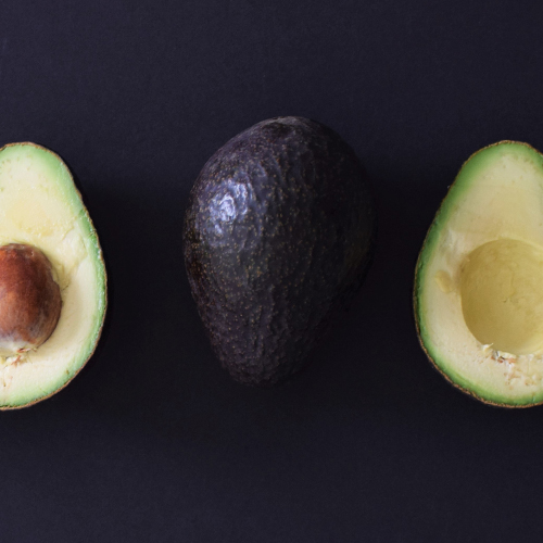 Top view image of a whole avocado and an avocado cut in half.