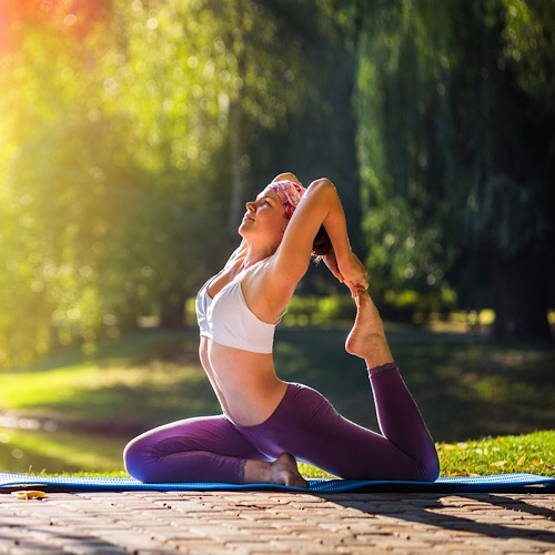 A woman doing Yoga outside under the morning sunlight wearing purple leggings and white sports bra.