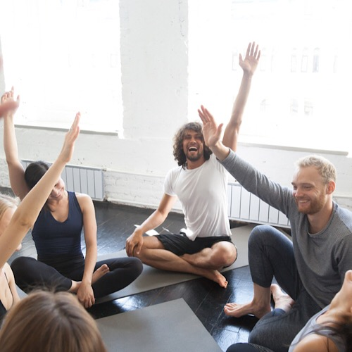 A group of people raising their hands after their yoga class.