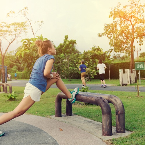 A woman doing her stretching outdoors before starting her morning jog