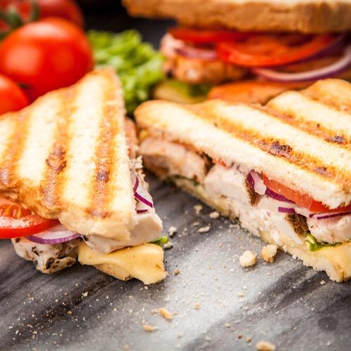 Chicken sandwich sliced in half.