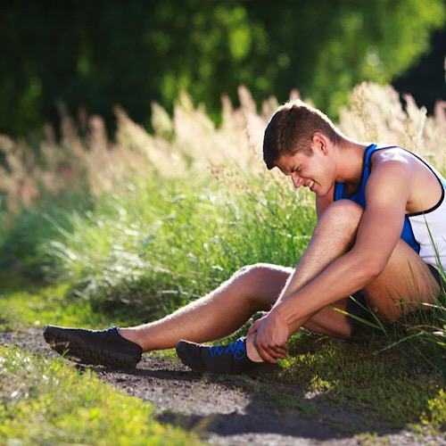 A runner holding his sprained ankle while sitting on the grass.