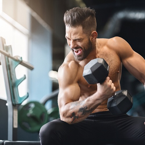Fit man using dumbbell.