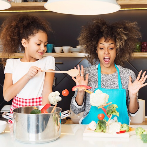 Beautiful African American woman and her daughter cooking in the kitchen.