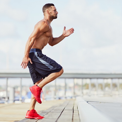 A fit man running in place outdoors.