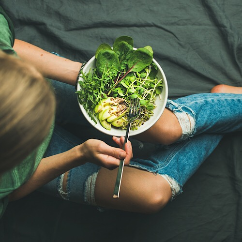 Green vegan breakfast meal in bowl with spinach, arugula, avocado, seeds and sprouts. Girl in jeans holding fork with knees and hands visible, top view. Clean eating, detox, vegetarian food concept - Image