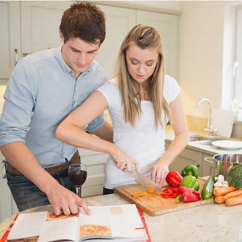 A young couple preparing their food while checking on a recipe book.