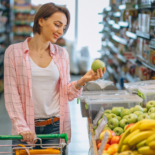 A woman doing her groceries while checking on a fruit.