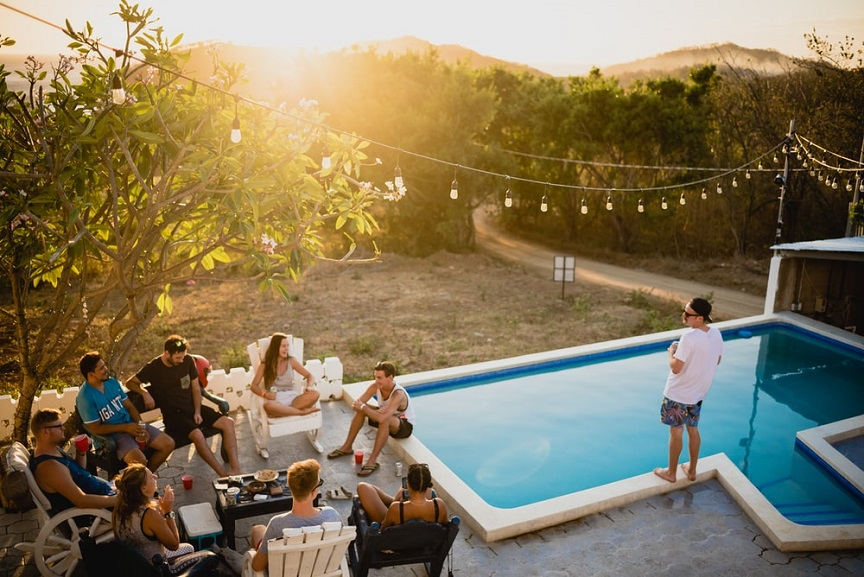 A group of people having some drinks next to a swimming pool during a summer sunset.