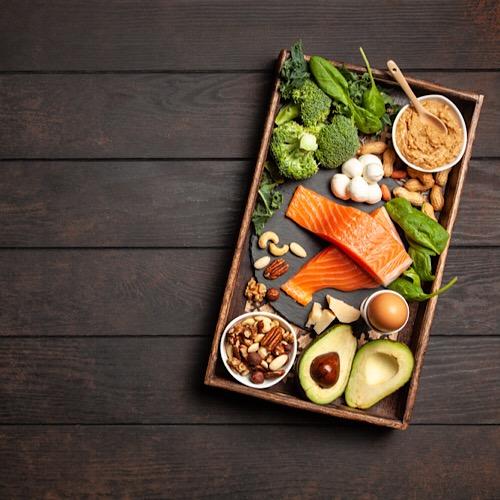 A tray of fresh healthy food like salmon, avocado, broccoli, nuts and egg