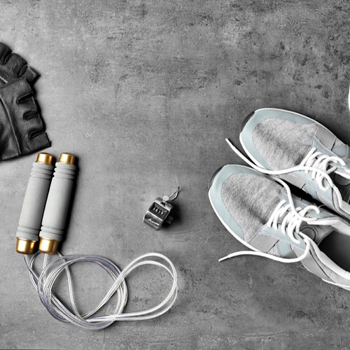 Gloves, jump rope and a pair of running shoes on the floor.