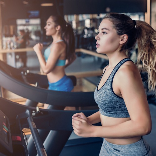 Two women running on treadmill.