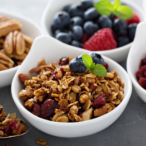 Bowls of berries, cereals and nuts.