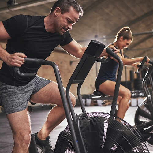 A couple training on an exercise elliptical bike.