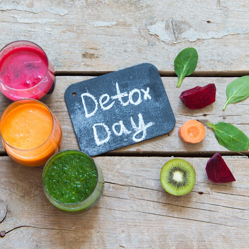"An image of text that says ""detox day"" in the middle with slices of fruits and 3 glasses of drinks."