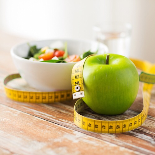 An apple, tape measure and a bowl of salad.