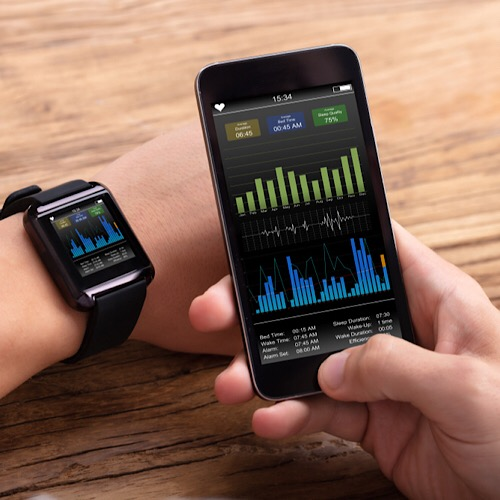 A man wearing a smart watch on his left hand and holding a smart phone on his right showing a fitness app and his progress.