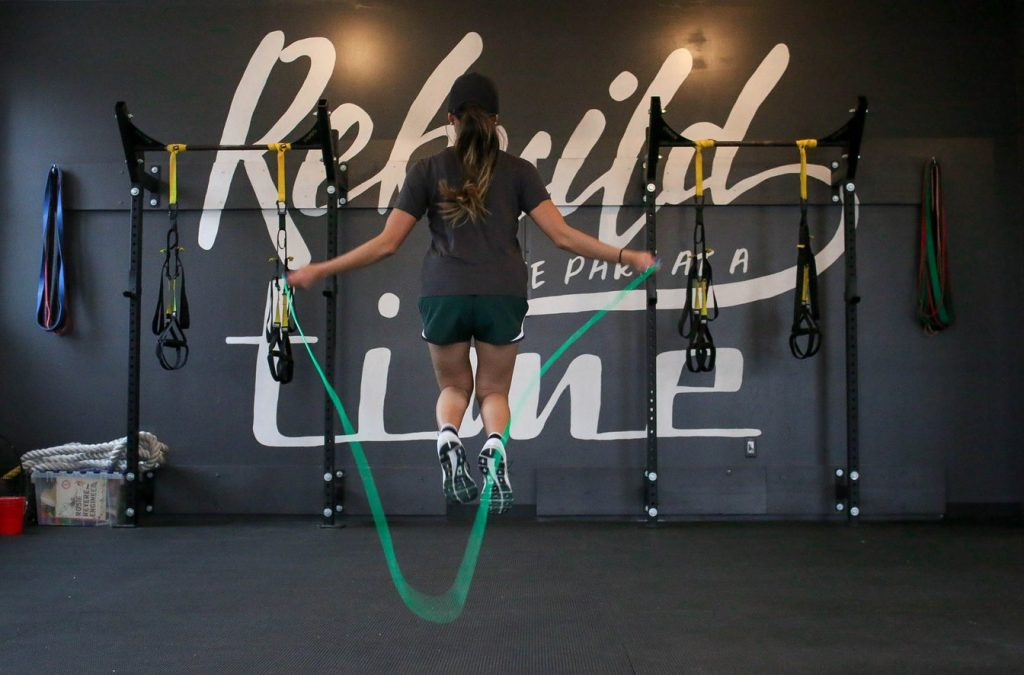 Woman doing jump rope exercise at the gym. Jump ropes are one of the best travel workout equipment.