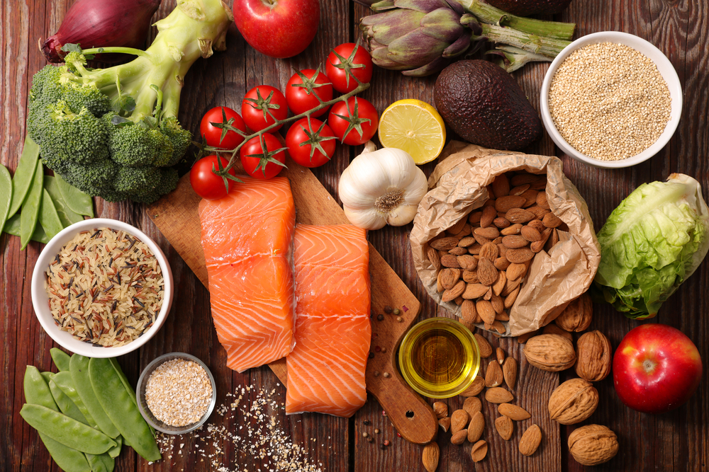 Healthy food like salmon, broccoli, tomatoes, nuts, avocado, lettuce on a wooden surface. Make sure you have enough vitamins and supplements in your diet.