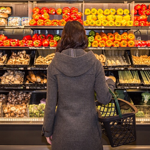 A back of a woman looking at a the fruits on the stand.