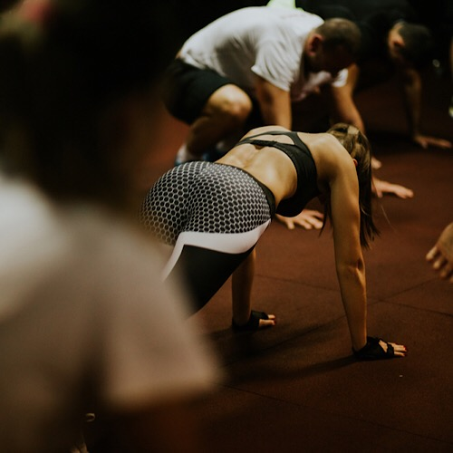 A fit woman doing push ups surrounded by other people at the gym.